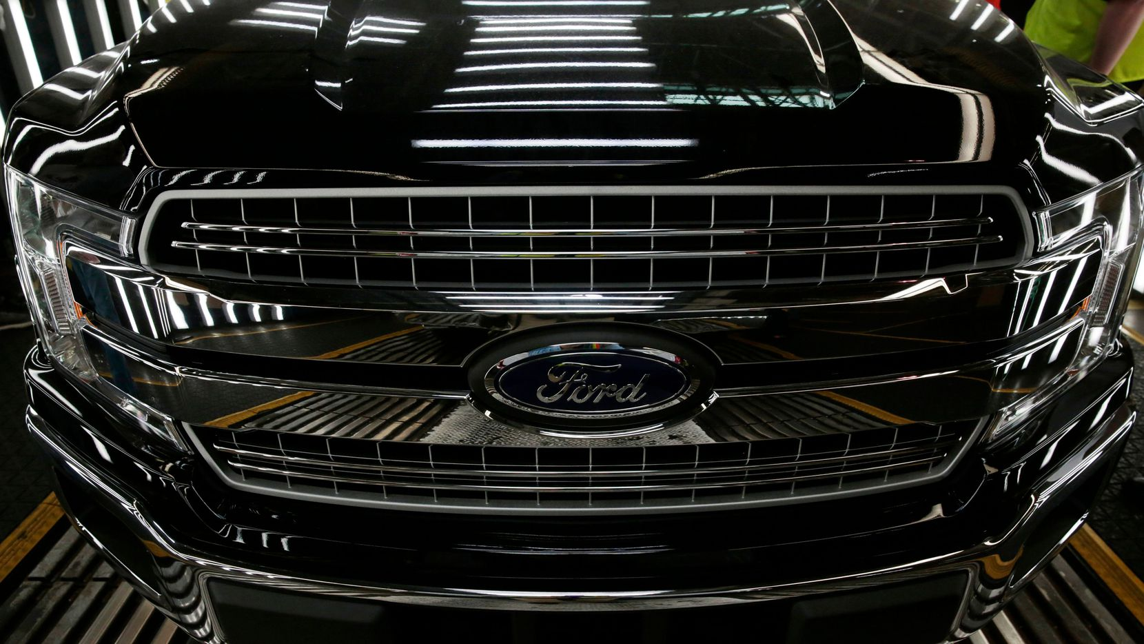 This file photo shows a Ford logo on a front bumper as Ford 2018 and 2019 F-150 trucks sit on the assembly line at the Ford Motor Company's Rouge Complex in Dearborn, Mich.