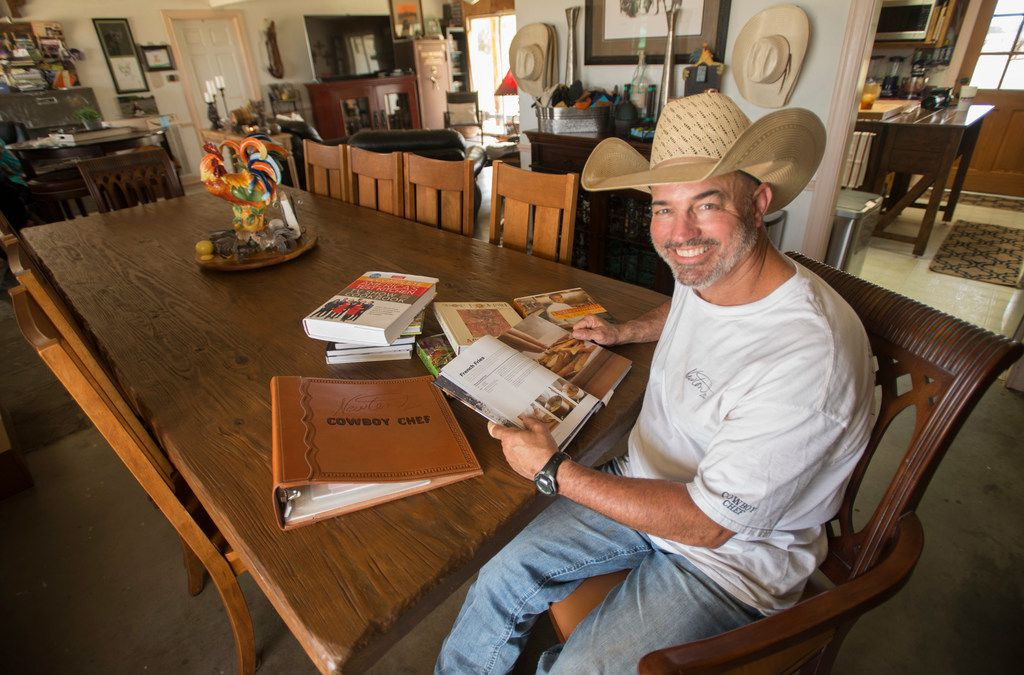 Mike Newton, known as the Cowboy Chef, studies cookbooks at the table where he and his wife Melanie serve guests in their ranch house in Lipan, Texas on July 17, 2018. (Robert W. Hart/Special Contributor)