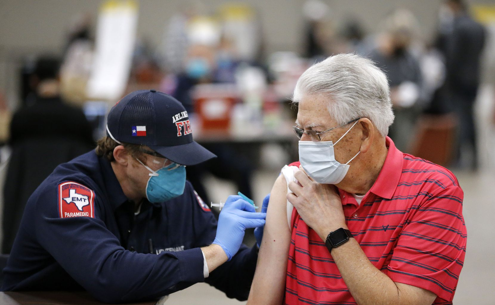 Jim Cox, 79, receives a COVID-19 vaccination from Arlington Fire Lt. Joshua Jones at Esports Stadium Arlington & Expo Center, a mass vaccination site in Arlington, Texas, Monday, January 11, 2021. The hub site is distributing over 2,000 vaccinations a day.