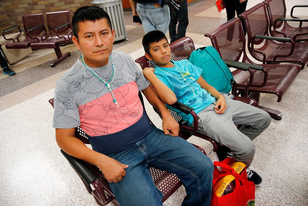 Central American immigrants Waldemar Cuztical and his son Walter Humberto, 12,  waited for transportation at the Central Station bus terminal in downtown McAllen, Texas, Sunday, June 24, 2018, after being reunited at the U.S. Border Patrol Central Processing Center. They spent six days apart in the facility. (Tom Fox/The Dallas Morning News)