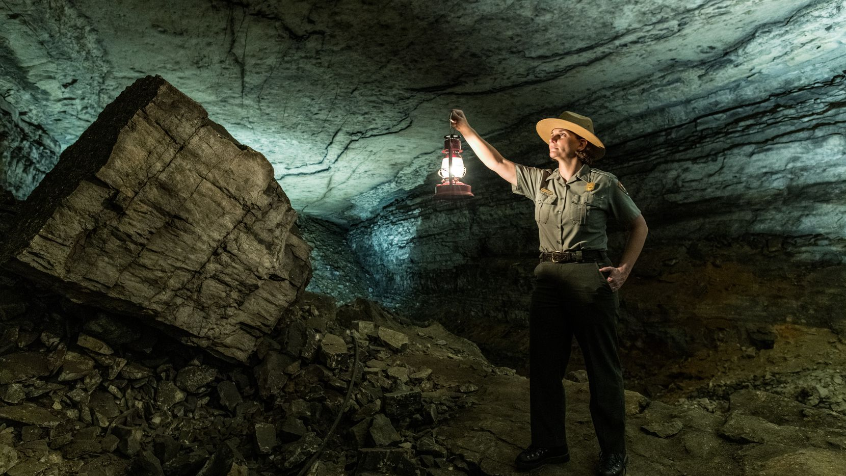 A tour guide illuminates the limestone walls inside Mammoth Cave.
