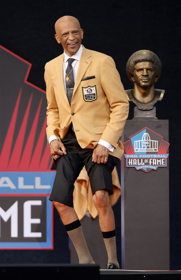 Pro Football Hall of Fame inductee Drew Pearson of the Dallas Cowboys hikes his pants to show off his still skinny legs during his speech at the Class of 2021 enshrinement ceremony in Tom Benson Hall of Fame Stadium in Canton, Ohio, Sunday, August 8, 2021. (Tom Fox/The Dallas Morning News)