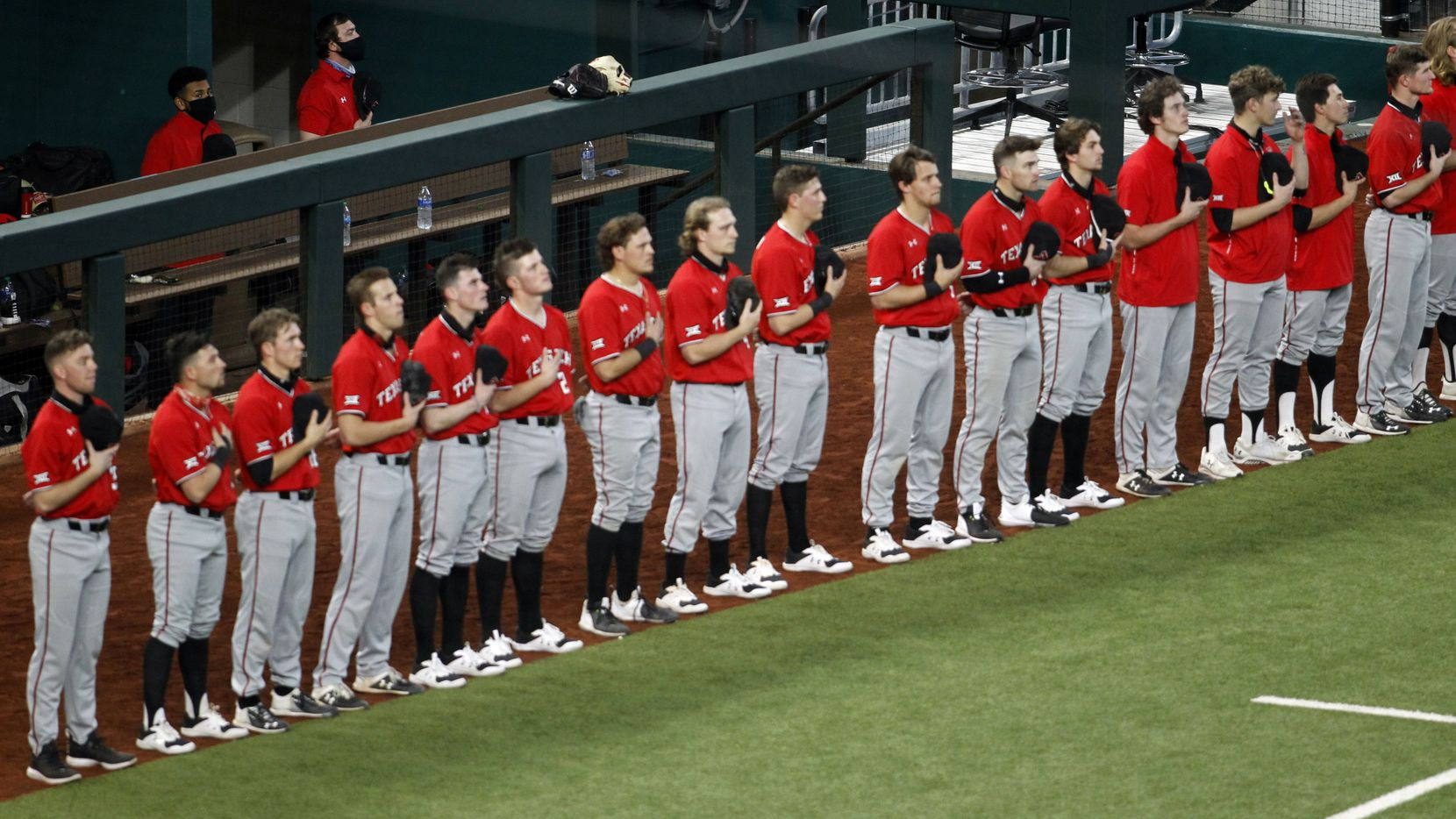 Members of the Texas Tech Red Raiders baseball team pause for the playing of the national anthem prior to the start of their game against Ole Miss. Texas Tech played Ole Miss in conjunction with the State Farm College Baseball Showdown tournament held at Globe Life Field in Arlington on February 21, 2021.