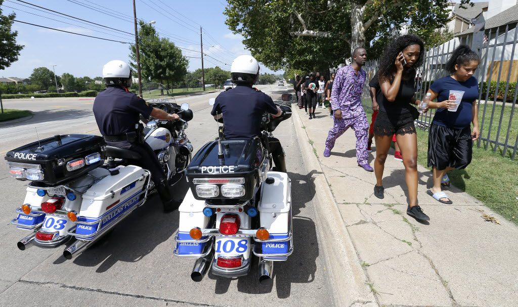 A group of a Black Lives Matter protesters walks by Dallas Police Department motorcycle Unit officers while they march on Fair Oaks Avenue in Dallas, Sunday, July 10, 2016. (Jae S. Lee/The Dallas Morning News)