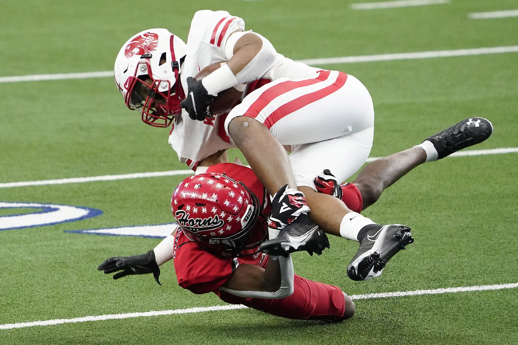 Katy running back Isaiah Smith (26) is knocked off his feet by Cedar Hill cornerback Amarian Williams (9) during the first half of the Class 6A Division II state football championship game at AT&T Stadium on Saturday, Jan. 16, 2021, in Arlington, Texas.