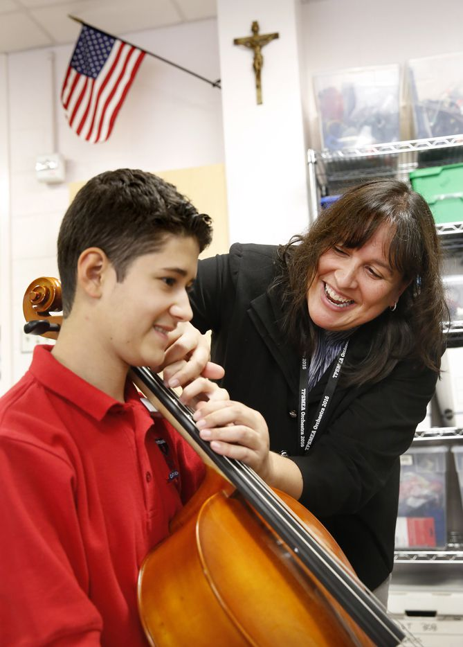 Instructor Julia Gray-Lion and  Zach laugh while working on finger placement during his second cello lesson at Bishop Dunne Catholic School. He plans to join the strings class when he gets to high school in the fall.
