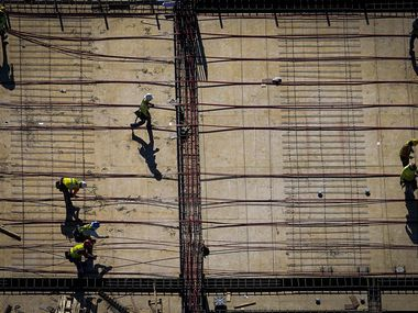 "An aerial view of construction workers near the American Airlines Center in March. While economic activity continues to decline and the outlook is ""bleak,"" according to the Beige Book, economists said the pace of decline is slowing."