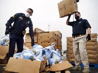 Dallas Police Department UNIDOS outreach team members Sgt. Eddie Reyes (left) and Lt. Stephen Williams unload frozen turkeys for volunteers from First Untied Bank, Hunger Busters and Canales Furniture during a Thanksgiving turkey handout in the Pleasant Grove area of Dallas, Saturday, November 21, 2020. The group has been working to build trust between the Latino community and police the past five years. (Tom Fox/The Dallas Morning News)