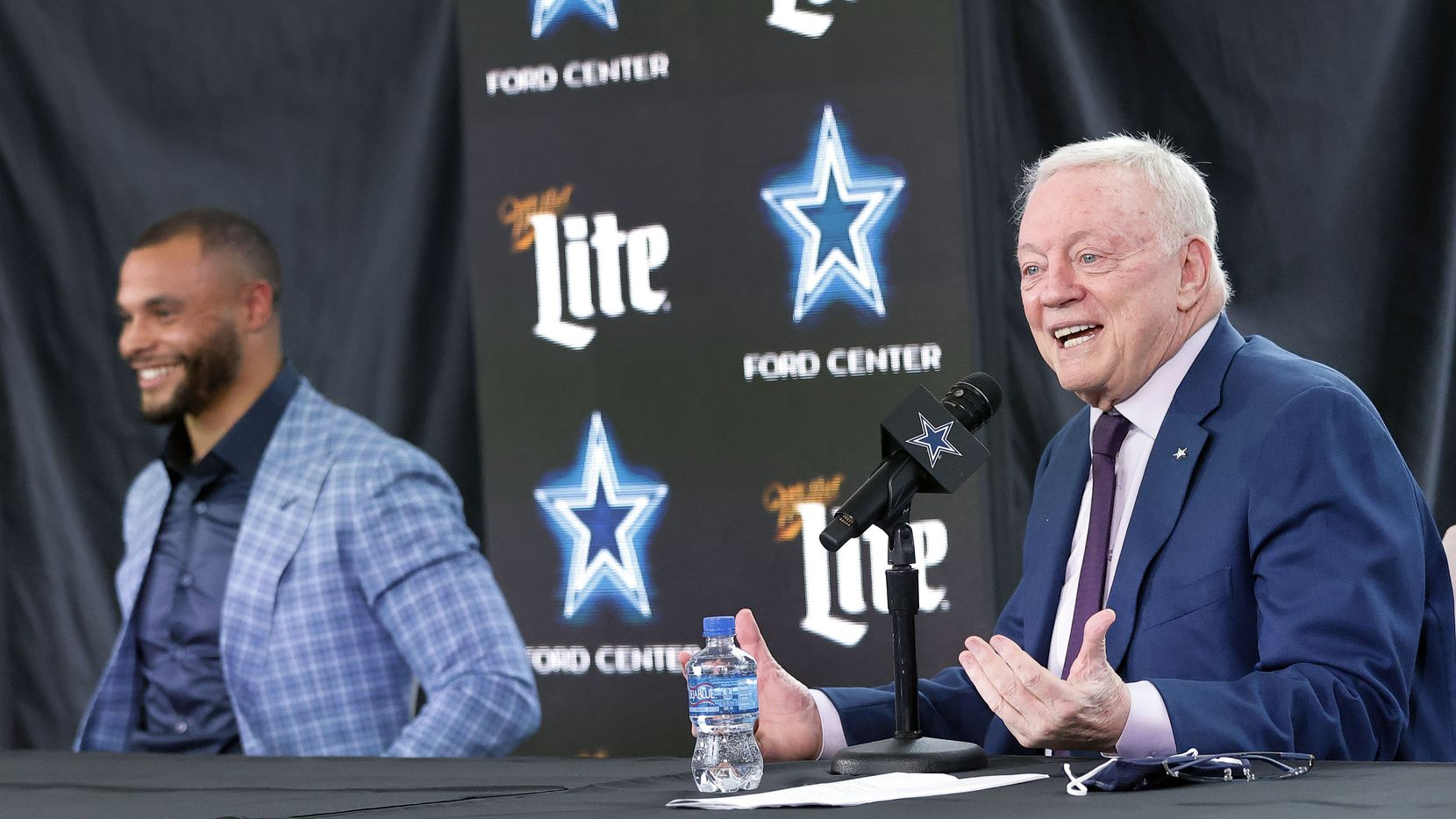 Dallas Cowboys owner Jerry Jones speaks about the signing of quarterback Dak Prescott (left) who laughs during his press conference at The Star in Frisco, Texas, Wednesday, March 10, 2021.