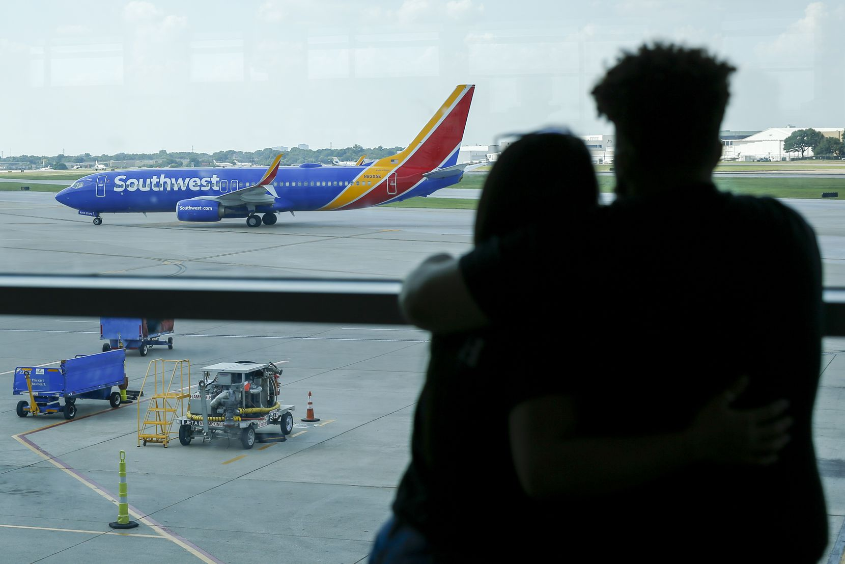 A couple watched as a Southwest Airlines flight taxied to the gate at Dallas Love Field on June 18.