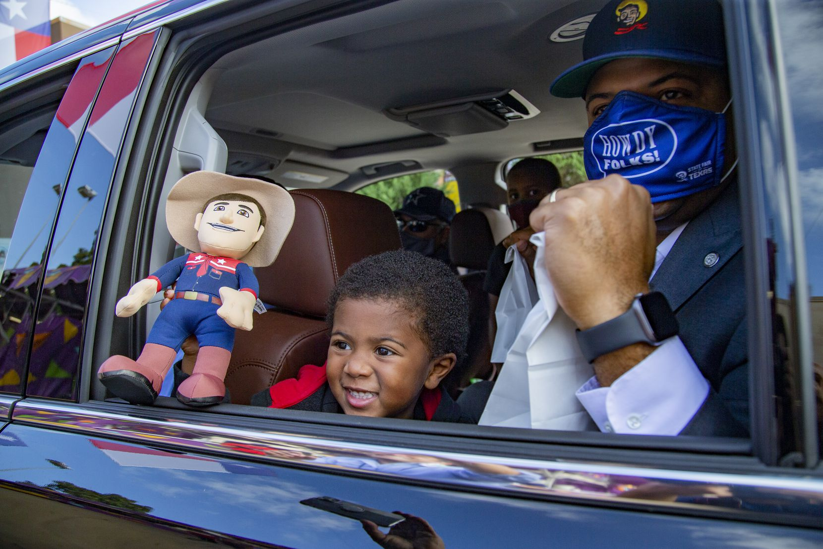 "Dallas Mayor Eric Johnson and son George waited for their Fletcher's Corny Dogs during the Big Tex Fair Food Drive-Thru at Fair Park in 2020 — an event hosted to ""keep the State Fair spirit alive"" despite the cancellation of the main event."