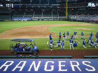 Texas Rangers players gather around field coordinator Matt Hagen following a game at the team's alternate training site at Globe Life Field on Saturday, Sept. 19, 2020.