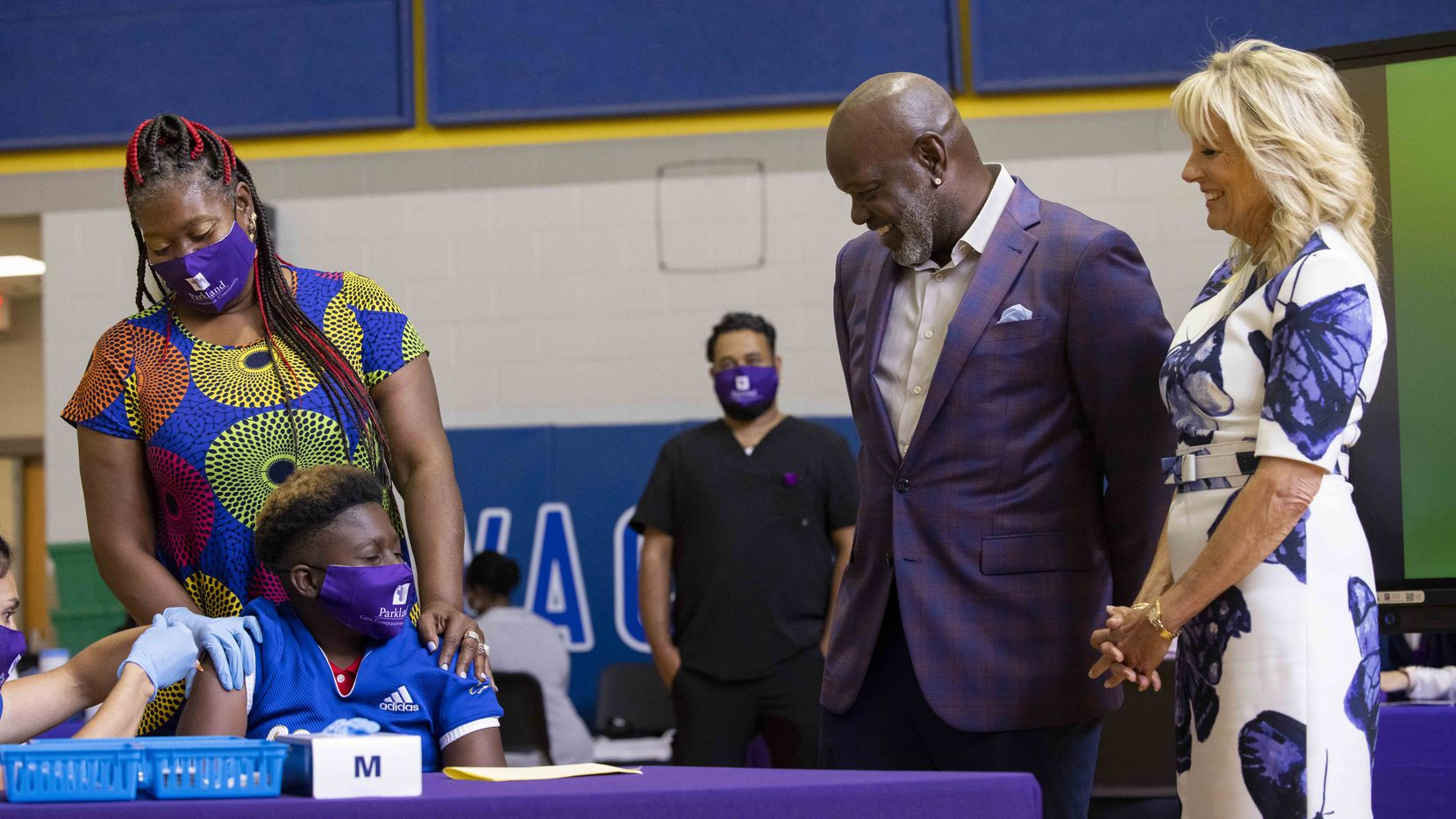 First lady Jill Biden and Dallas Cowboys legend Emmitt Smith watched as Ramona Williams held son Chase Walton as he received the COVID-19 vaccine June 29 during a tour of the vaccination site at Emmett J. Conrad High School in Dallas.
