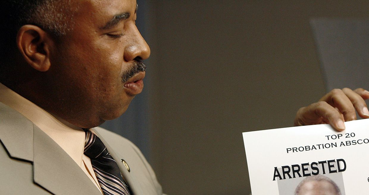 Anthony Robinson, chief investigator for the Dallas County District Attorney's office, displays a sheet containing photos of two of the top 20 probation absconders during a 2007 news conference at the Dallas County Sheriff's Department.