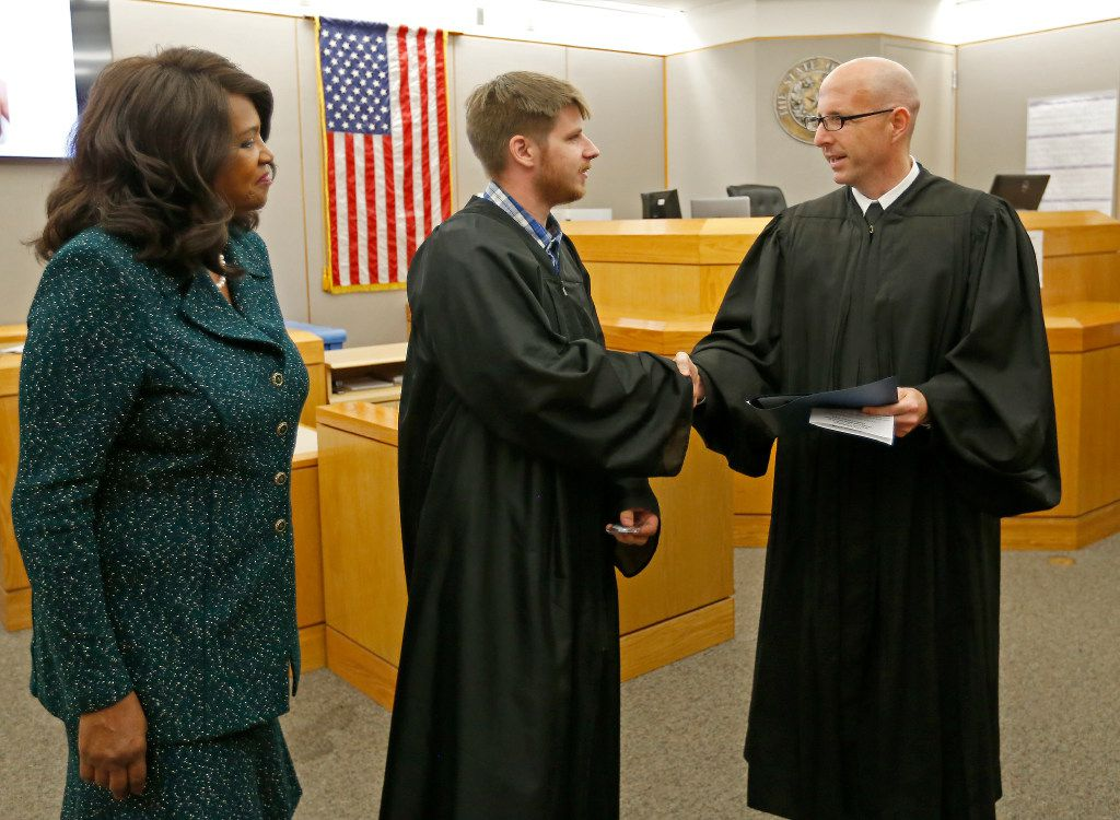 Judge Brandon Birmingham (right) shakes hands with Charles Troutman (center) as Dallas County District Attorney Faith Johnson looks on during a graduation ceremony of the Achieve Inspire Motivate program at 292nd Judicial District Court in Dallas, Monday, May 15, 2017. Troutman was charged with Impersonating a Public Servant in 2015 and his case has been dismissed after he completed the program. (Jae S. Lee/The Dallas Morning News)