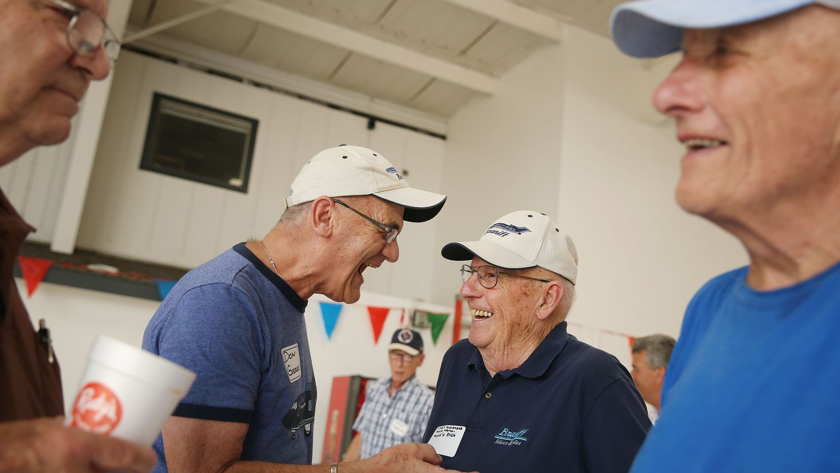 Don Gieseke (center left) and Dick Strohmeier, both retired Braniff pilots, shared a laugh during the 41st annual Braniff International Airways pilots picnic at Denton Municipal Airport in Denton on Monday.
