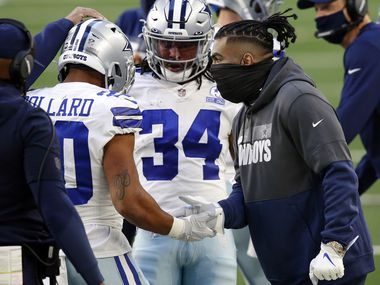 Injured Dallas Cowboys running back Ezekiel Elliott (right) congratulates fellow running back Tony Pollard (20) on his first quarter touchdown run against the San Francisco 49ers at AT&T Stadium in Arlington, Texas, Sunday, December 20, 2020.