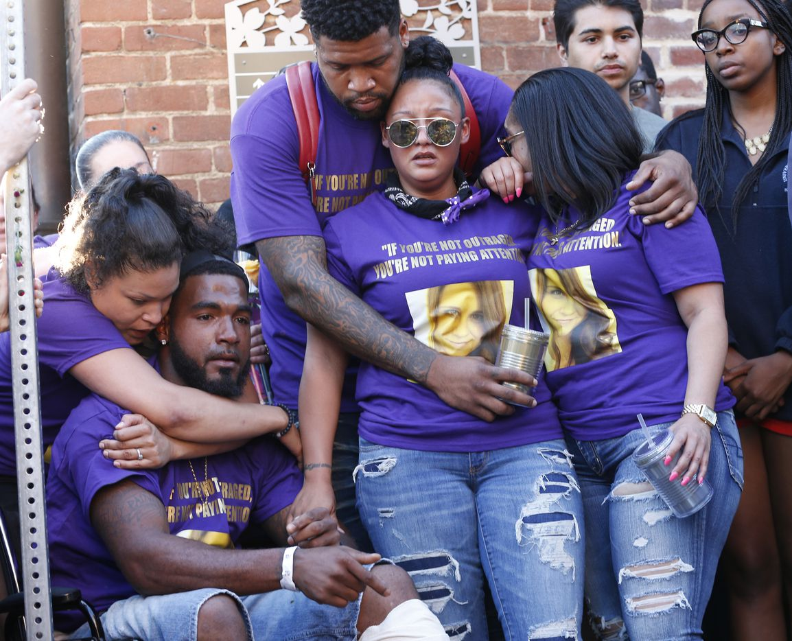 Marcus Martin, bottom left, pauses during a vigil on Sunday, Aug. 13, 2017, held for the victims injured Saturday in Charlottesville, Va. A car plowed into a crowd of people protesting a white supremacist rally on Saturday, injuring over a dozen people including Martin.