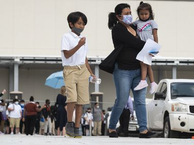A mother walks with her children after her son's first day back at ED Walker Middle School in Dallas.  Texas' under-18 population has grown 6% over the past decade, but that number has declined by 2% in Dallas County, according to recent census data.