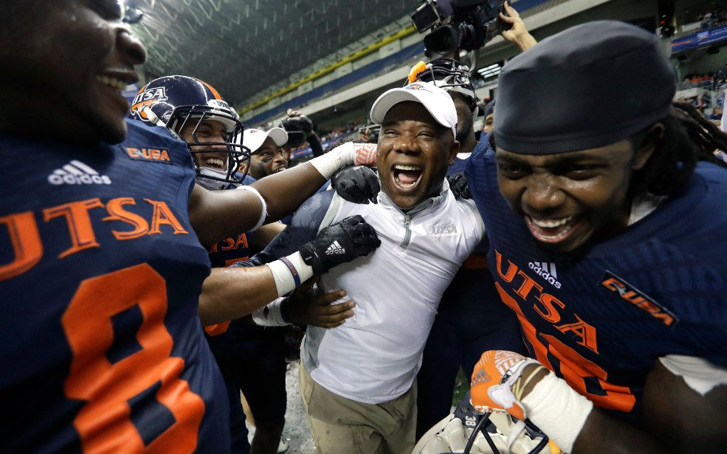 UTSA head coach Frank Wilson, center, and his players celebrate their win over Charlotte in an NCAA college football game, Saturday, Nov. 26, 2016, in San Antonio. UTSA won 33-14, making them bowl eligible for the first time in the history of their football program. (AP Photo/Eric Gay) ORG XMIT: TXEG112