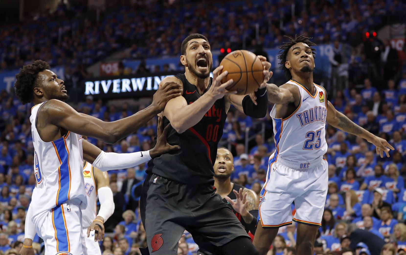 Portland Trail Blazers center Enes Kanter, center, Oklahoma City Thunder forward Jerami Grant, left, and guard Terrance Ferguson, right, compete for a rebound in the second half of Game 4 of an NBA basketball first-round playoff series Sunday, April 21, 2019, in Oklahoma City. Portland won 111-98. (AP Photo/Alonzo Adams)