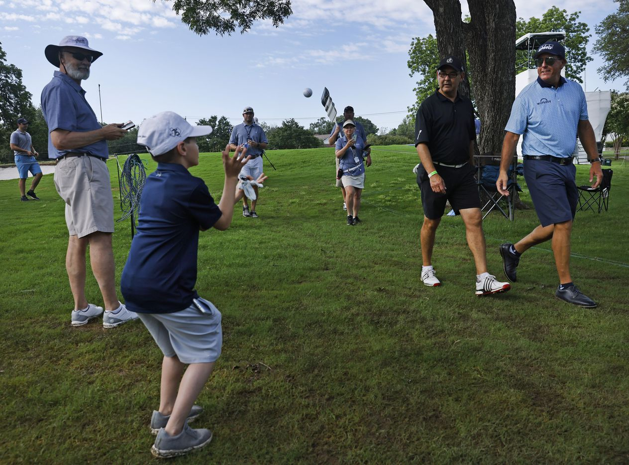 Golfer Phil Mickelson (right) tosses his golf ball to 10 yr-old Carson Woody of Hillsboro, Texas after putting out on No. 17 in the Charles Schwab Challenge Colonial Pro-Am at the Colonial Country Club in Fort Worth, Wednesday, May 26, 2021. Mickelson kept his commitment to play in the tourney after winning the PGA Championship last week. (Tom Fox/The Dallas Morning News)