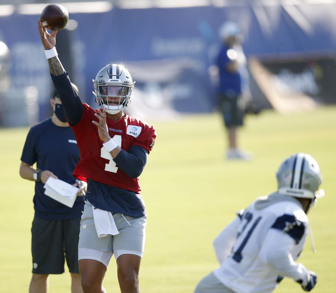 Dallas Cowboys quarterback Dak Prescott (4) passes to Dallas Cowboys running back Ezekiel Elliott (21) during the first day of training camp at Dallas Cowboys headquarters at The Star in Frisco, Texas on Friday, August 14, 2020. (Vernon Bryant/The Dallas Morning News)
