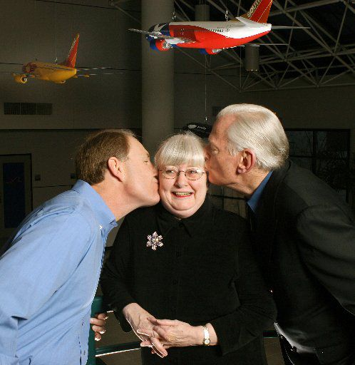 Gary Kelly Chief Executitive Officer and Herb Kelleher chairman, give Colleen Barrett, president, a kiss on the cheek in the lobby of the comapany's headquarters in Dallas.