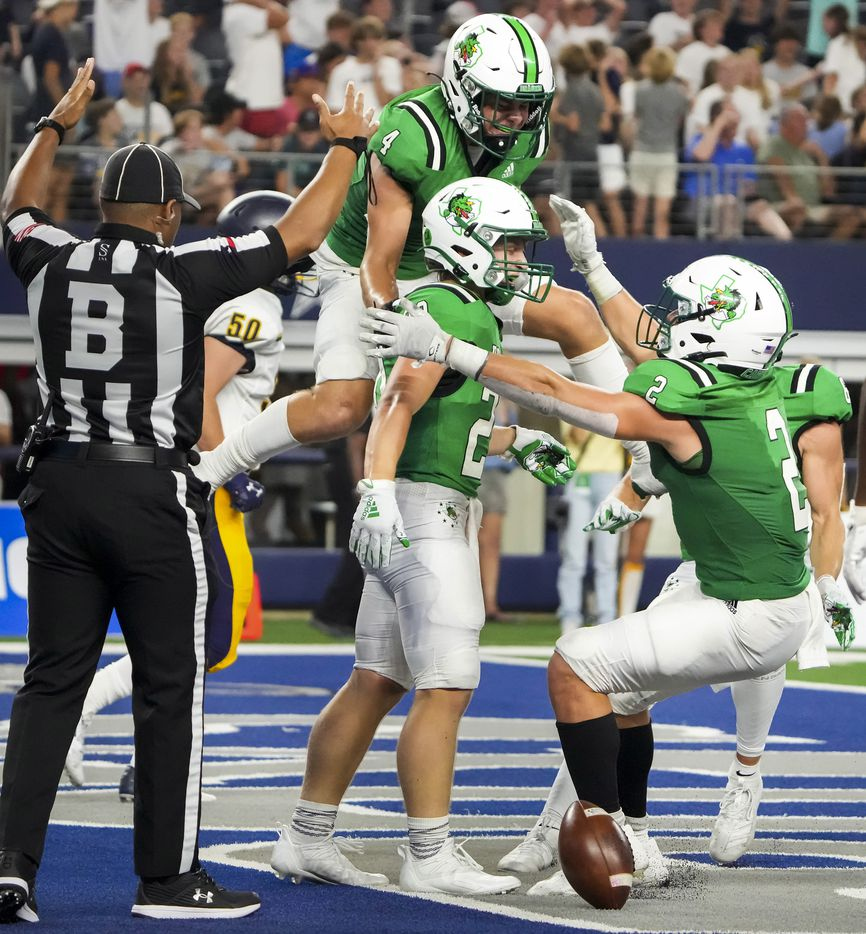 Southlake Carroll running back James Lehman (20) celebrates with wide receiver Owen Ohser (4) and running back Owen Allen (2) after making a one-handed catch for a touchdown during the first half of a high school football game against Highland Park at AT&T Stadium on Thursday, Aug. 26, 2021, in Arlington.