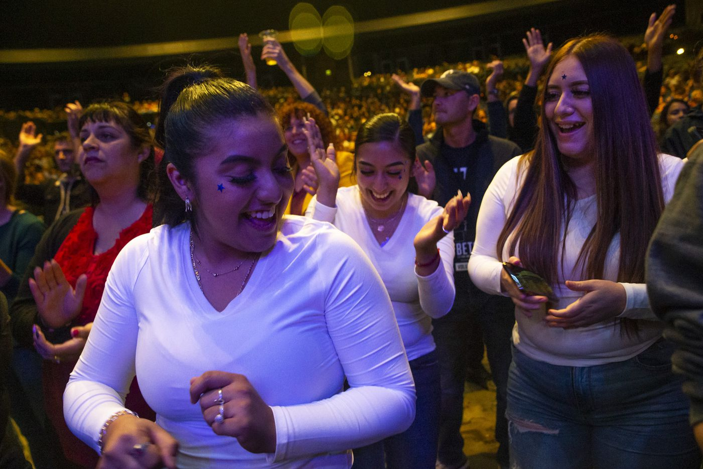 (From left) Yadenny Ocampo, Erica Ocampo and Giselle Figueroa, all from Dallas, dance to a musical performance during the Rally Against Fear event hosted by Democratic presidential candidate and former Texas Rep. Beto O'Rourke in the Theatre at Grand Prairie on Thursday, Oct. 17, 2019, in Grand Prairie, Texas. O'Rourke hosted the event in response to President Donald Trump's rally in downtown Dallas at the same time.