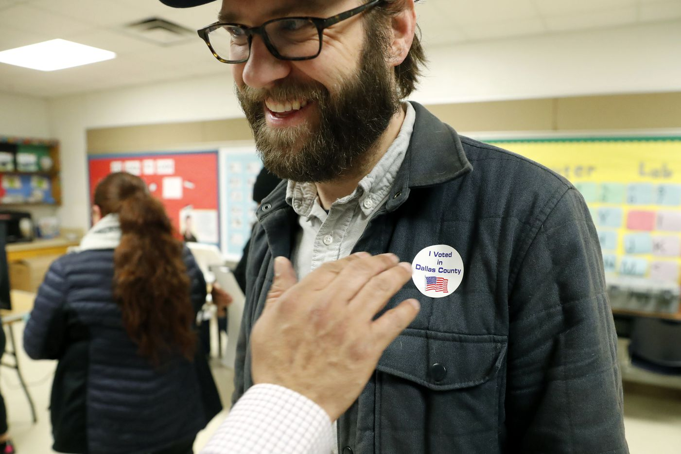 Democrat Jamie Wilson gets a sticker after voting in the Super Tuesday primary at John H. Reagan Elementary School in the Oak Cliff section of Dallas, Tuesday, March 3, 2020.