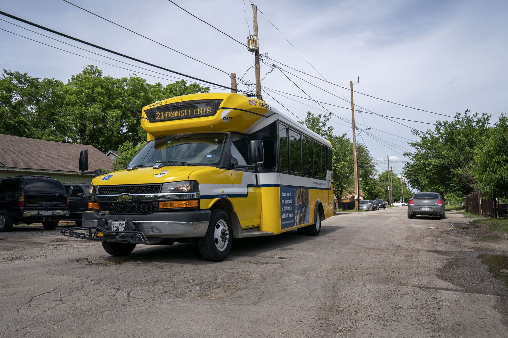 A DART bus drives down Nolte Drive, just north of the Tyler-Vernon transit station. The street is filled with potholes as a result of bus traffic, and residents lack the curbing and sidewalks that would keep schoolchildren safe from vehicles.