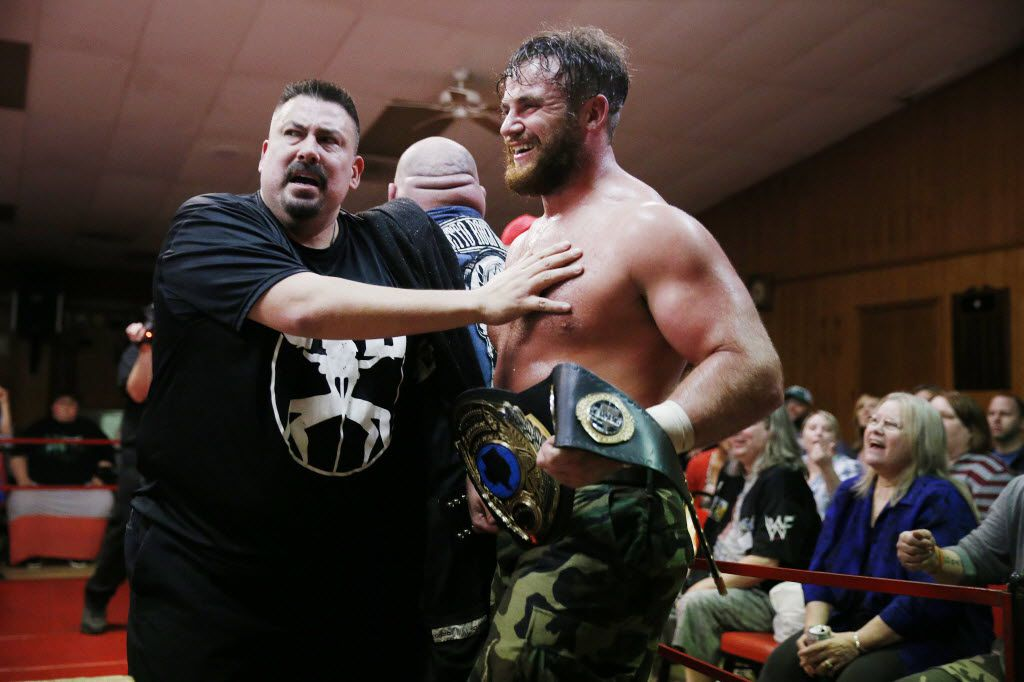Professional wrestler Moonshine Mantell (right), whose real name is Ryan Greeness, is held back by promoter Lance Romance as he celebrates a tag team match victory with teammate Killer McKenzie (center, back) at a National Wrestling Alliance event at the Sherman Elks Lodge. The NWA puts on matches at the Elks Lodge every third Friday of the month.