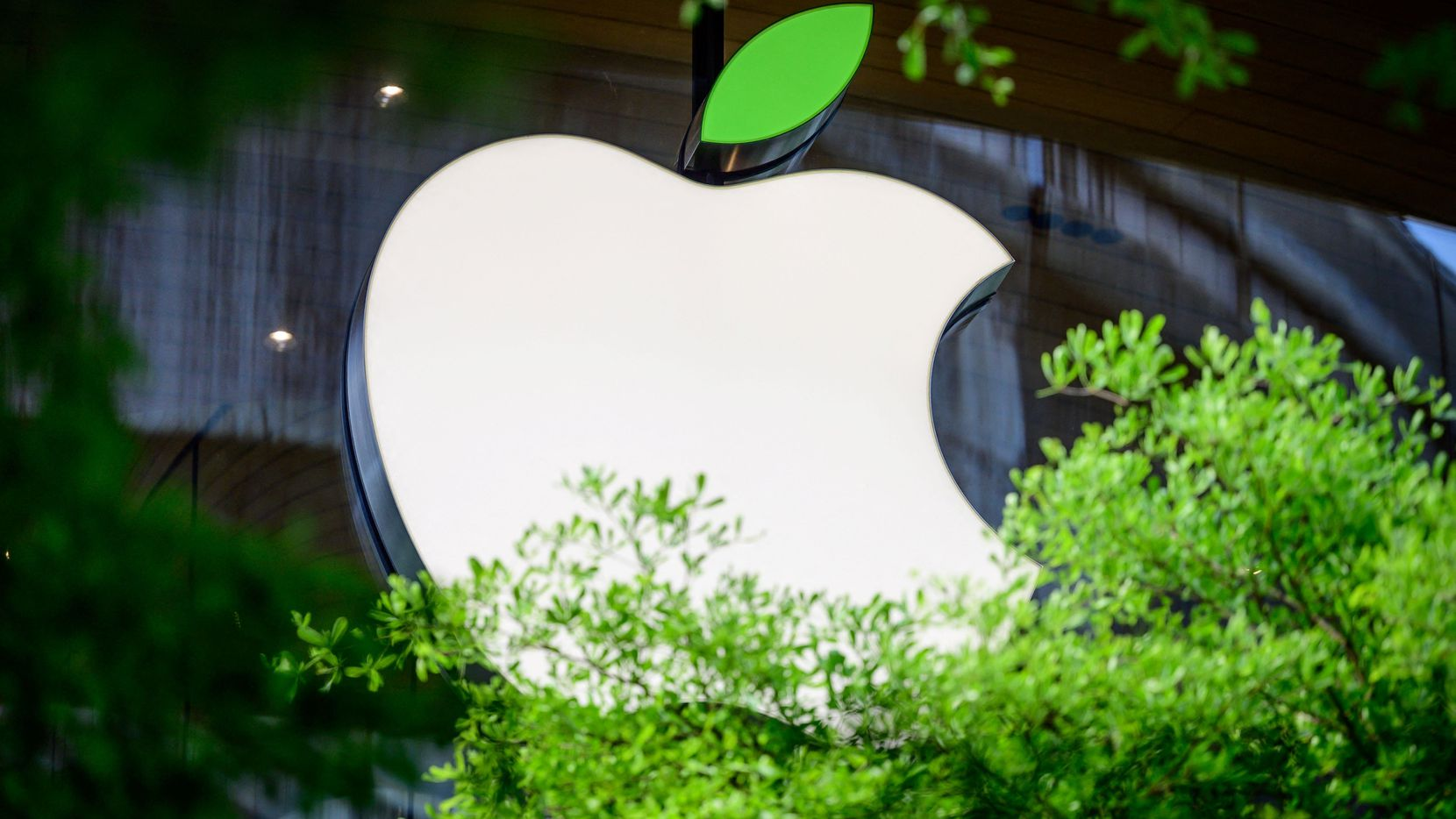 The Apple logo sporting a green leaf to mark the upcoming Earth Day is seen on a window of the company's store in Bangkok.