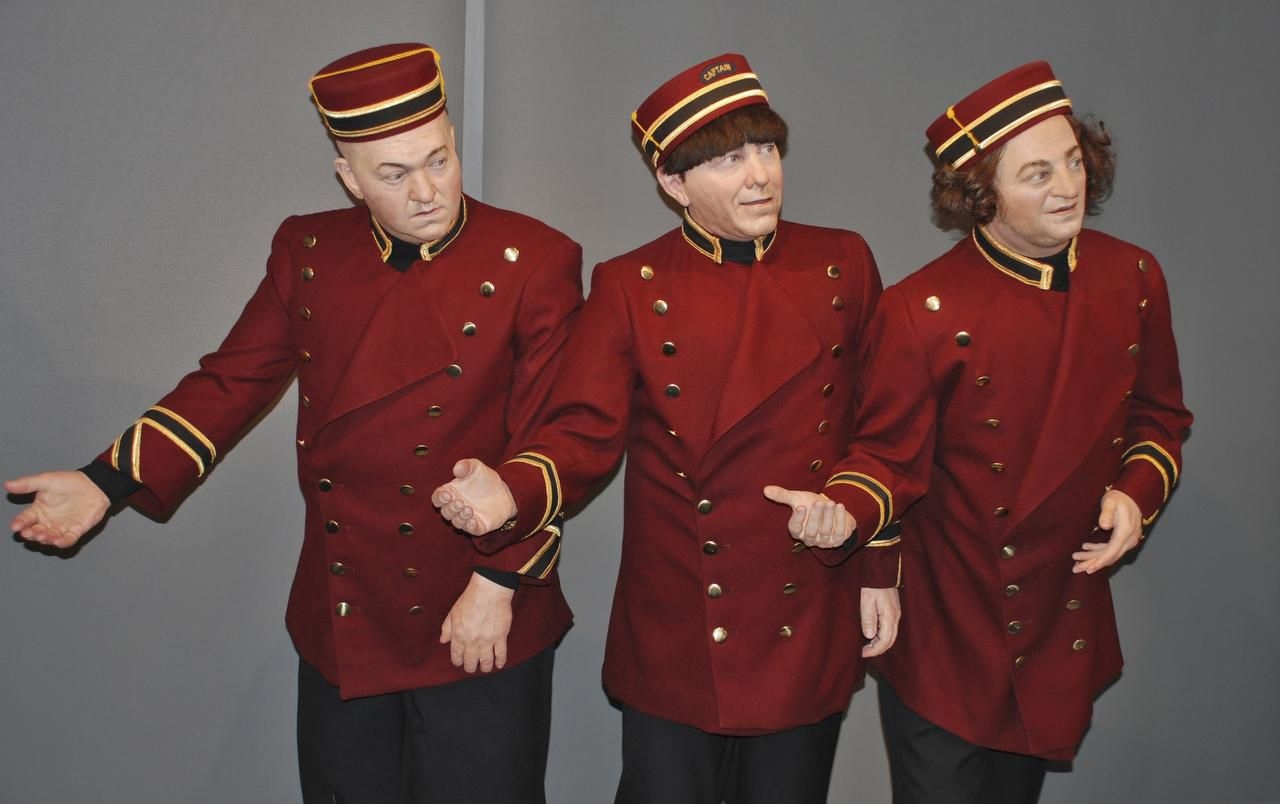 Wax figures  of Curly, Moe and Larry, dressed as bellboys, bow in welcome to visitors at the Stoogeum.