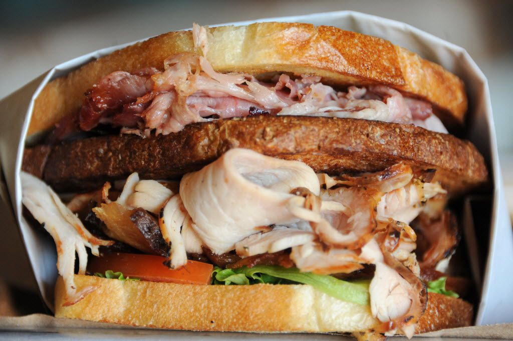 The Club sandwich features bacon, turkey, ham, lettuce, tomato, bacon mayo, and mustard on white and wheat bread at Goodfriend Package in Dallas, TX on January 13, 2016.