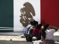 A migrant woman brushes her hair as she and other expelled migrants sit at a plaza near the international bridge leading into the Mexican border city of Reynosa on Wednesday, March 31, 2021. The U.S. continues to expel migrants under Title 42 — a pandemic-related public order still in place and left over from the Trump administration.