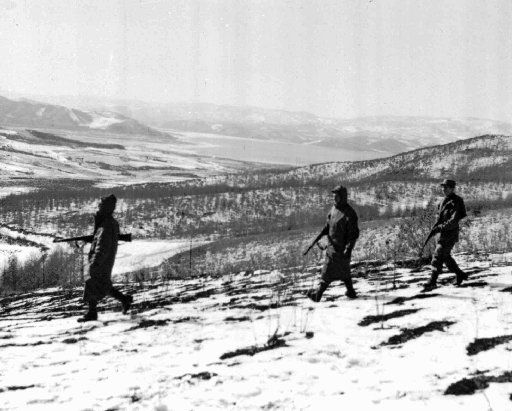 Marines patrol the icy hills near North Korea's Chosin Reservoir, which is visible in background in this Nov. 27, 1950 file photo.