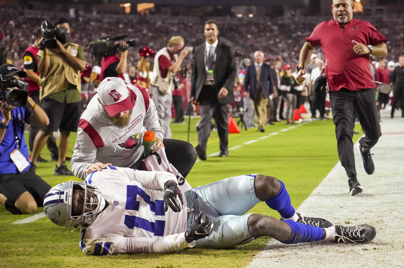 Arizona Cardinals training staff rush to the aid of Dallas Cowboys wide receiver Malik Turner (17) after he was injured on a pass play during the second half of a preseason NFL football game at State Farm Stadium on Friday, Aug. 13, 2021, in Glendale, Ariz.