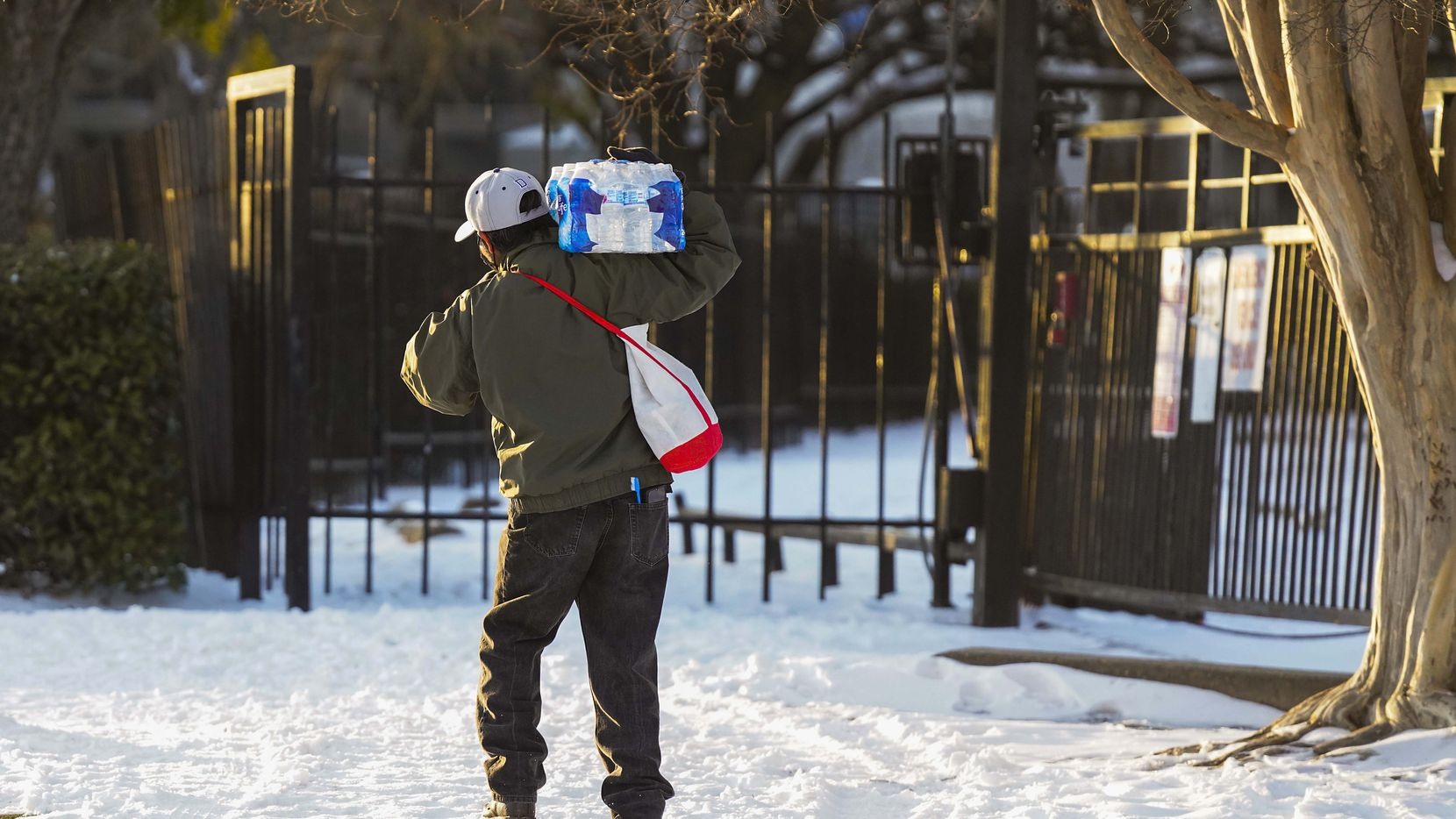 A man walks home with a case of drinking water distributed at the Literacy Achieves nonprofit in Vickery Meadow to nearby residents living without water after a winter storm brought snow and continued freezing temperatures to North Texas in February.