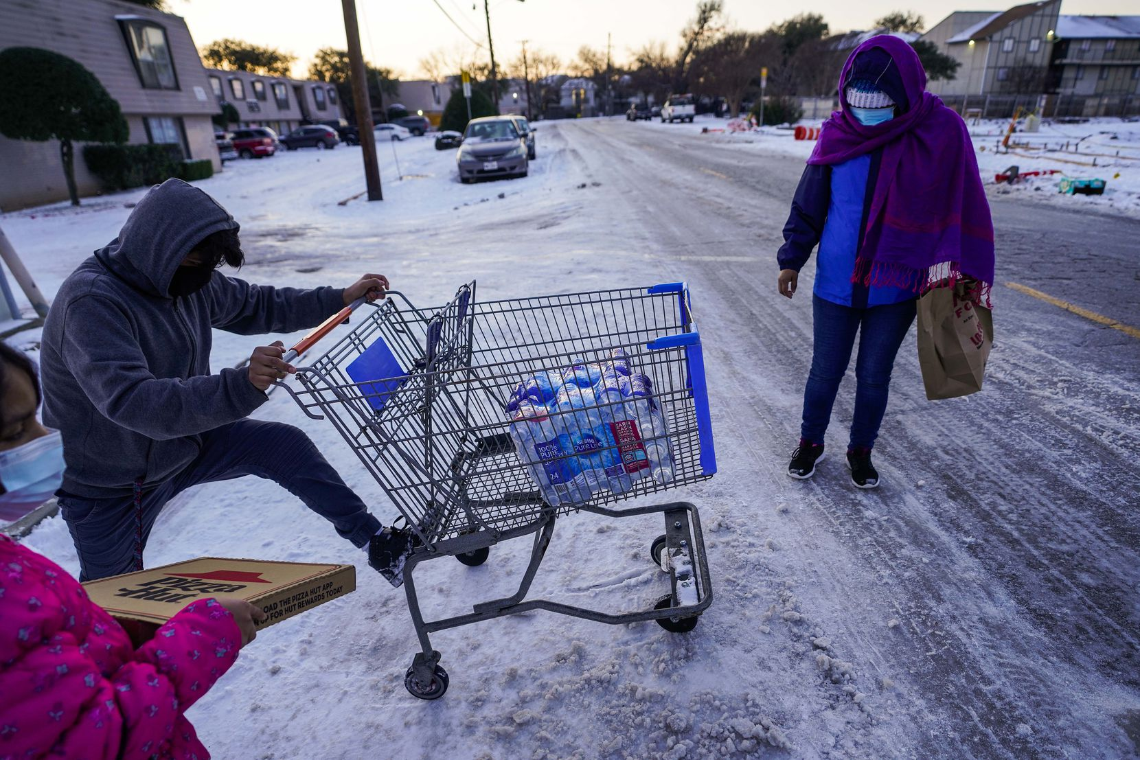 Juan Carlos Gonzalez pushes a shopping cart with two cases of drinking water, distributed at the Literacy Achieves nonprofit in Vickery Meadows to nearby residents living without water, home to his family after a winter storm brought snow and continued freezing temperatures to North Texas on Thursday, Feb. 18, 2021, in Dallas.  (Smiley N. Pool/The Dallas Morning News)