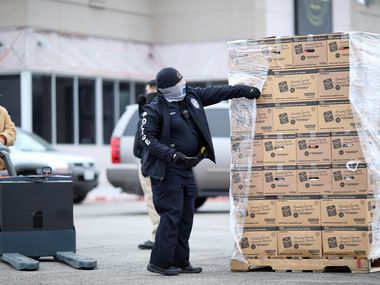The Dallas Police Department distributes pallets of food to pantries in the Far West parking lot in Pleasant Grove. Pallets of food were stolen from Comforter Christian Center last week the night before its weekly food distribution.