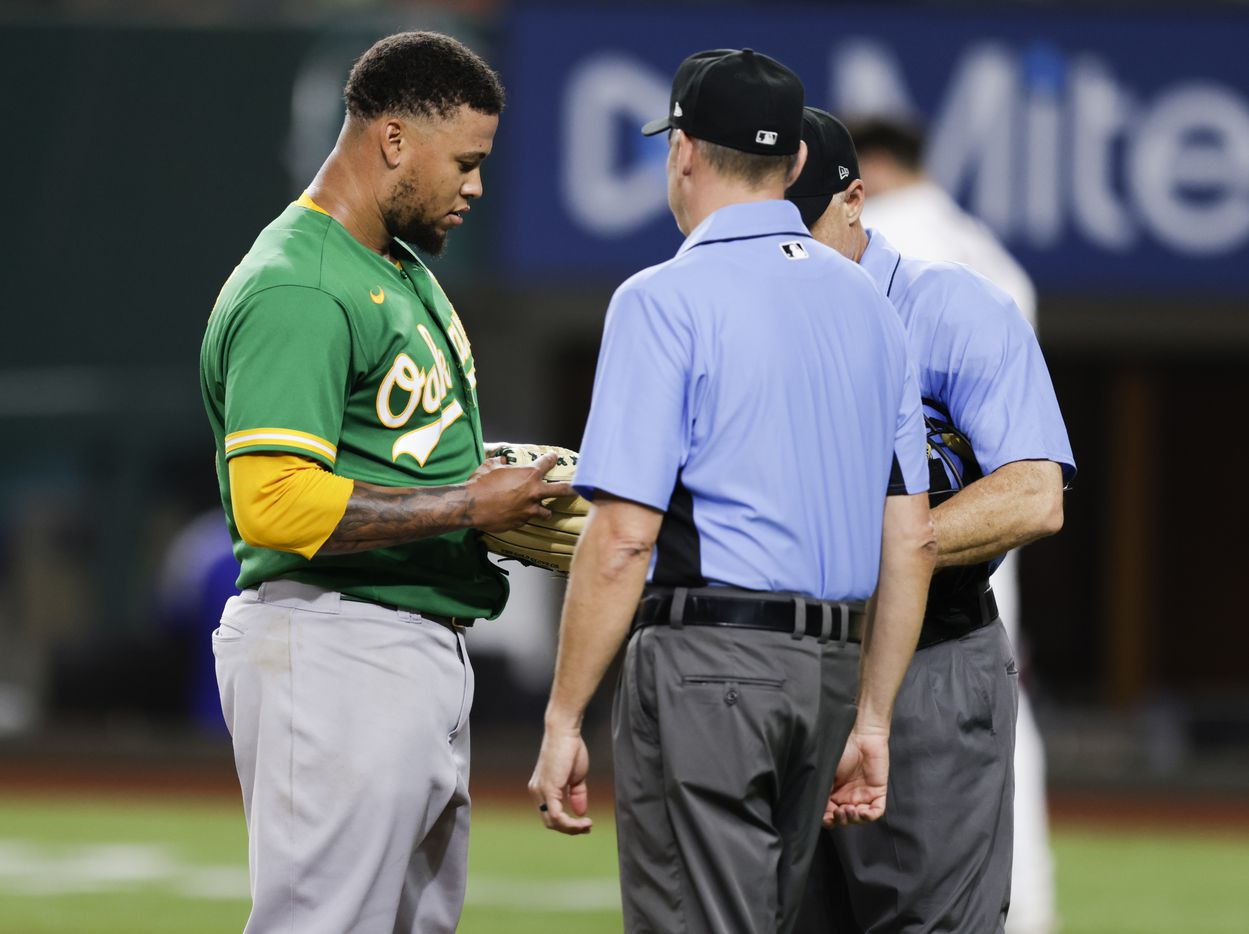 Home plate umpire Dan Iassogna and third base umpire Andy Fletcher inspect Oakland Athletics starting pitcher Frankie Montas' (47) glove after the fifth inning of a baseball game against the Texas Rangers in Arlington, Monday, June 21, 2021. (Brandon Wade/Special Contributor)