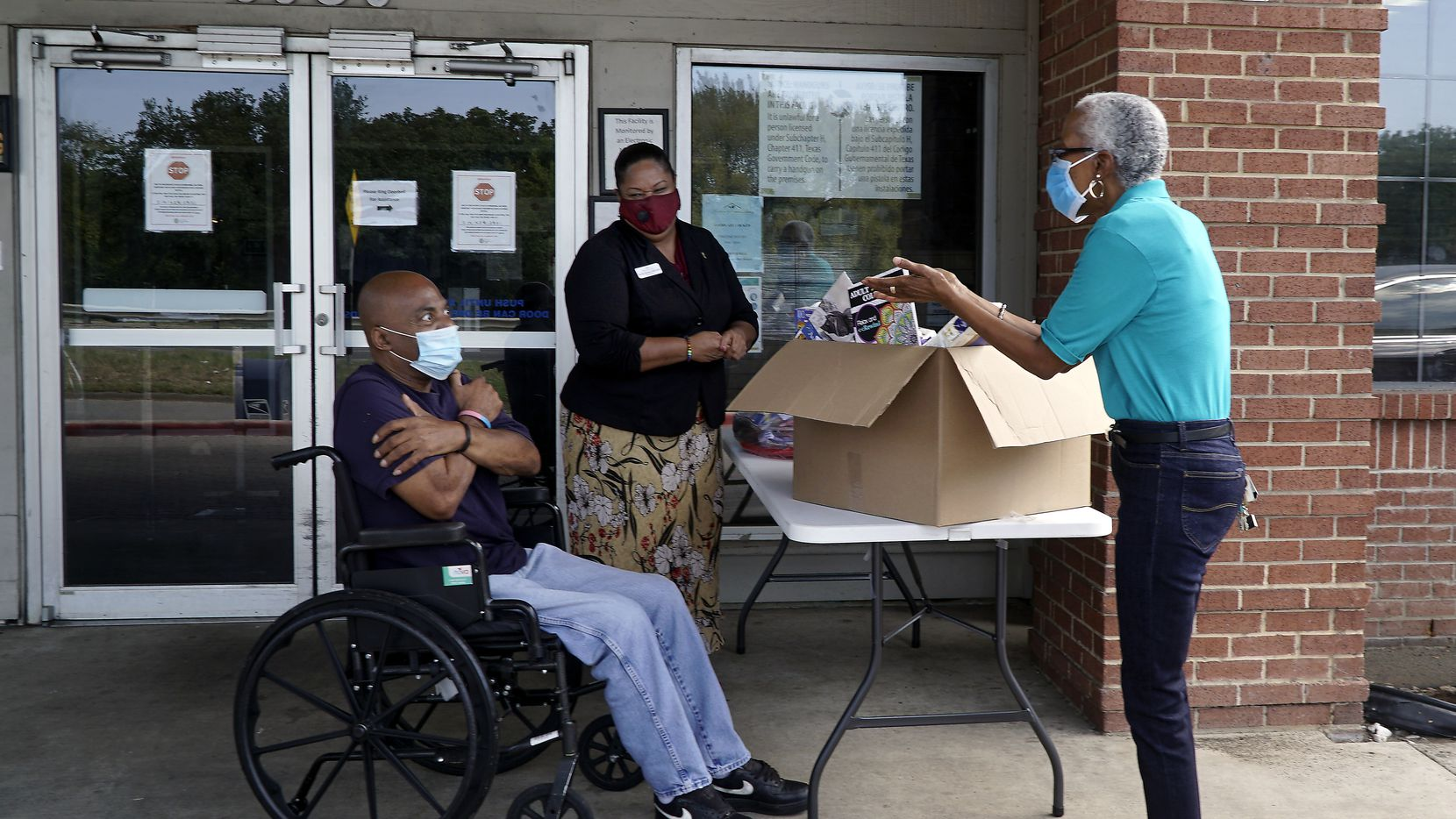 """Marsha Evans (right), Friendly Visitor Program manager for the Senior Source, shares a safe """"hug"""" with Modern Senior Living resident Willie Wilson (left) and administrator Monté Mitchell. Evans was delivering donations.."""