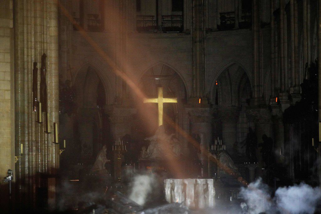 Smoke rises around the altar in front of the cross inside Notre Dame Cathedral as debris from the roof continues to burn on the floor on April 16, 2019