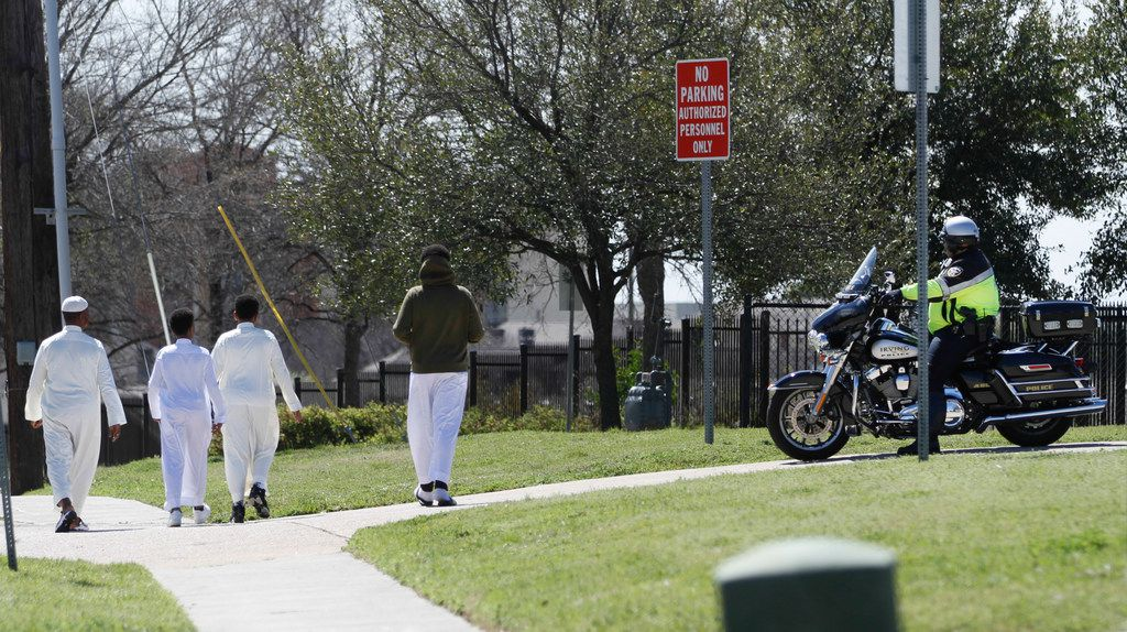 A family heads toward the Islamic Center of Irving for afternoon prayers as an Irving motorcycle officer stands watch