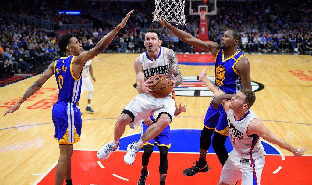 El guardia de los Clippers de Los Ángeles, J.J. Redick, pasa por en medio de dos jugadores de los Warriors de Golden State en un partido efectuado el 2 de febrero de 2017.