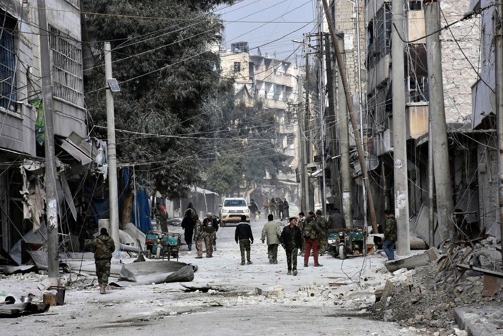 This photo released by the Syrian official news agency SANA, shows Syrian soldiers and civilians marching through the streets of east Aleppo, Syria, Monday, Dec. 12, 2016. (SANA via AP)