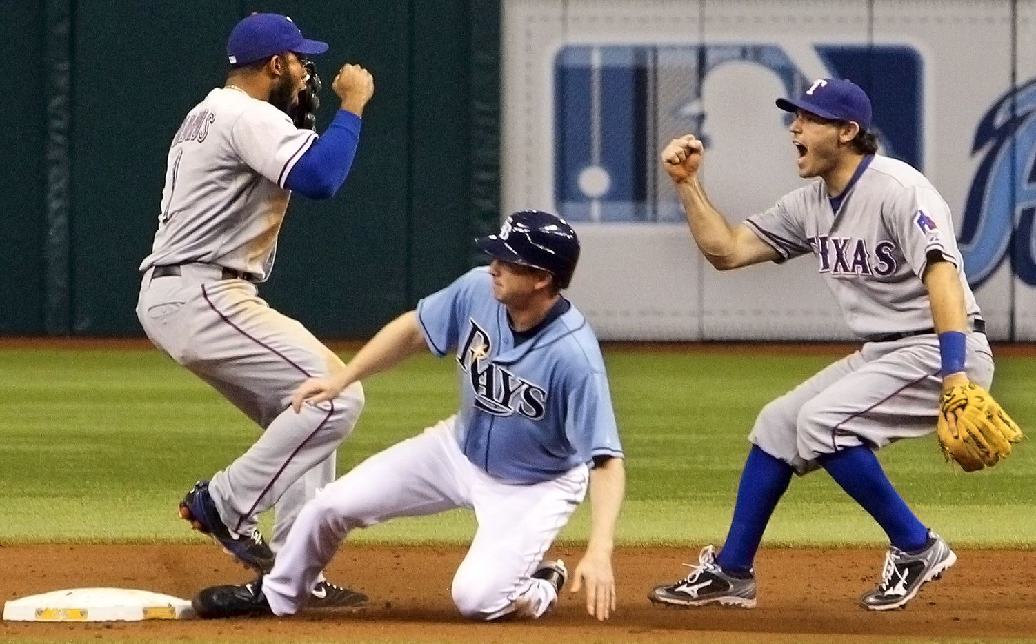 Texas SS Elvis Andrus, left, and 2B Ian Kinsler, right, celebrate the final out at second as Tampa pinch runner Elliot Johnson slides in on the final play in Texas' 4-3 ALDS-clinching win during Game 4 of the American League Division Series between the Texas Rangers and the Tampa Bay Rays on Tuesday, October 4, 2011 at Tropicana Field in St. Petersburg, FL. (Louis DeLuca/The Dallas Morning News)