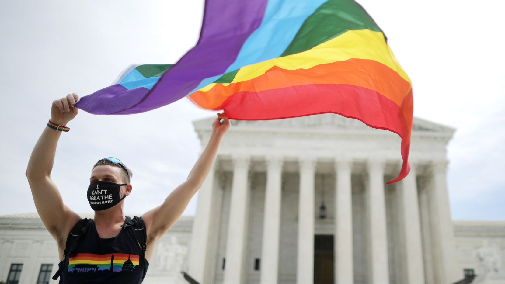 Joseph Fons, holding a Pride Flag, stands in front of the U.S. Supreme Court building after the court ruled that LGBTQ people can not be disciplined or fired based on their sexual orientation June 15, 2020 in Washington, DC. With Chief Justice John Roberts and Justice Neil Gorsuch joining the Democratic appointees, the court ruled 6-3 that the Civil Rights Act of 1964 bans bias based on sexual orientation or gender identity.